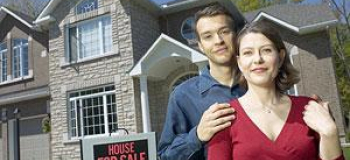 Couple in front of house and for sale sign